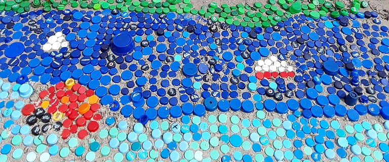 Am Strand lassen die Schülerinnen und Schüler farbenfrohe Environmental Art entstehen