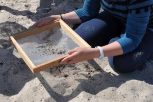 Eine Schülerin siebt am Flussufer Mikroplastik aus